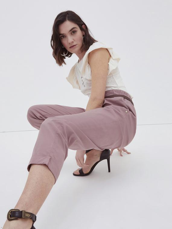 Pantaloni in gabardina di cotone stretch; modello carrot a vita alta; dettaglio paper bag e cintura in similpelle con fibbia; tasche anteriori verticali.