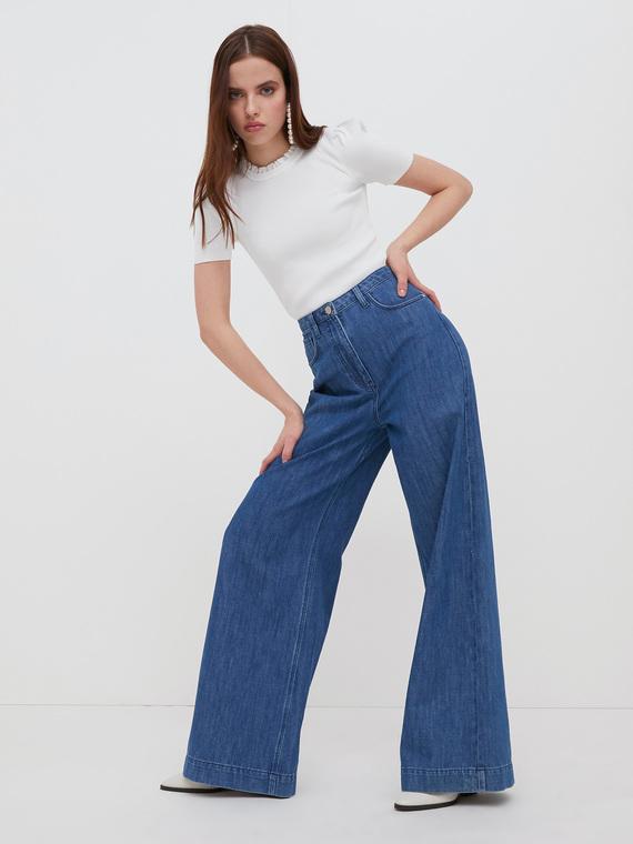 Jeans gamba palazzo in denim di cotone; modello cinque tasche; accessori in metallo canna di fucile.