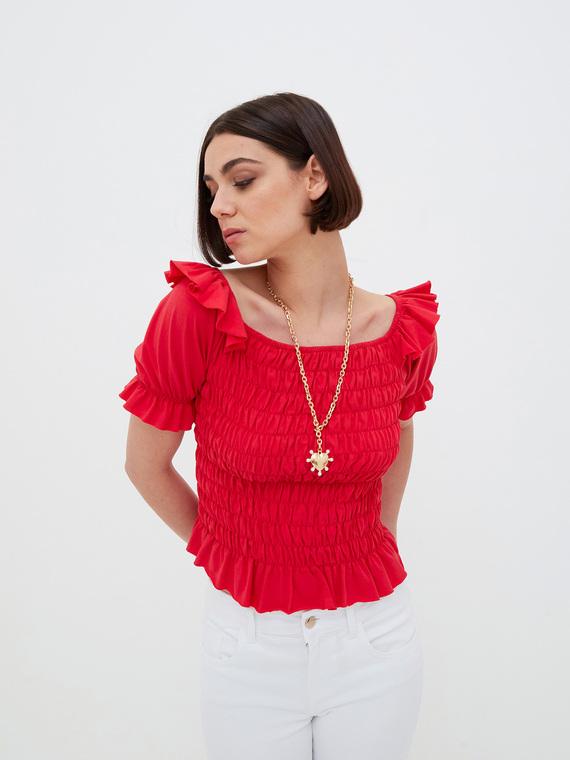 T-shirt corta in jersey di cotone; ampio scollo con maniche corte a palloncino; motivo di impunture elastiche sul corpino.
