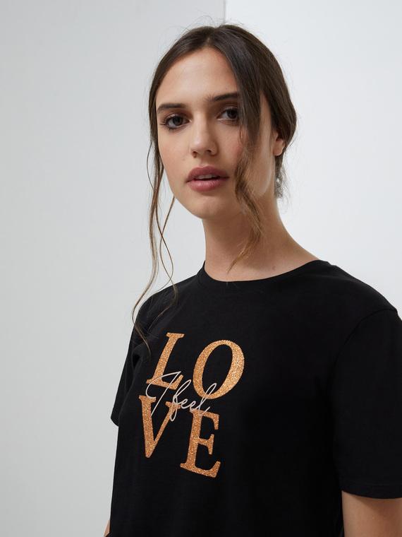 T-shirt in jersey 100% cotone; modello con scollo tondo e manica corta; stampa frontale lettering con glitter.