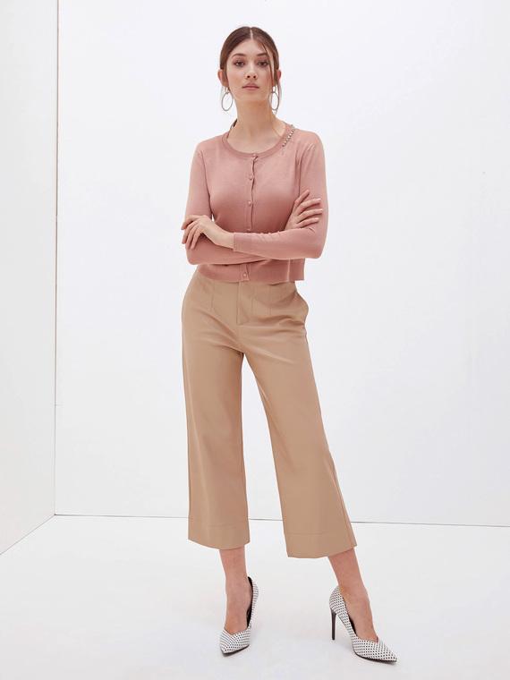 Pantaloni in morbida similpelle; modello cropped con gamba larga e vita alta; apertura frontale con bottone foderato e zip; tasche a filetto sul retro.