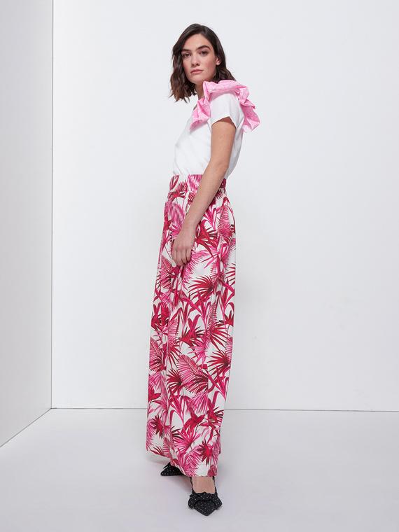 Pantaloni in cotone fantasia palme; gamba palazzo; vita con elastico inserito nel retro; tasche verticali inserite nel fianco.